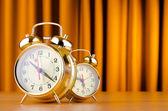 Alarm clock against curtain — Stock Photo