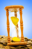 Time is money concept - hourglass and coins — Stock Photo