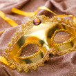 Golden mask on the satin background — Stock Photo