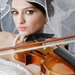 Bride playing violin in studio - Stockfoto