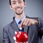 Man with piggybank on grey — Stock Photo #9375677