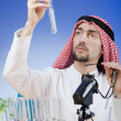 Arab chemist working in lab - Stock Photo