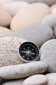 Navigation compass on stone pebbles — Stock Photo