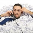 Man with lots of waste paper - Stockfoto