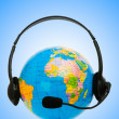 Headset on globe isolated on the white - Stock Photo