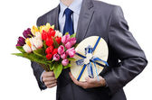 Businessman with giftbox and flowers — Stock Photo
