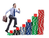 Businessman climbing stacks of casino chips — Stok fotoğraf