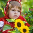 Little girl in a smart Sarafan is among sunflowers — Stock Photo #8383489