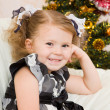 图库照片: Little girl at a Christmas fir-tree.