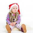 Little blonde girl in a fur jacket and a red Santa's cap sits on — Stock Photo #8384351