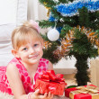 Girl with gifts near a New Year tree — Stockfoto