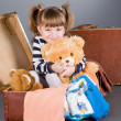 Girl joyfully sits in an old suitcase — Stock Photo #8384894