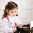 Little girl prints on the ancient typewriter — Stock Photo #8385294