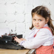 Little girl prints on the ancient typewriter — Stock Photo #8385299