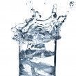 Ice splashing in cup of water — Stock Photo