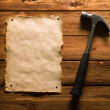 Hammer and old paper on wood - Stock Photo