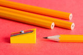 Pencils, pencil sharpener on red — Stock Photo