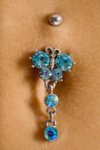 Female navel with piercing — Stock Photo