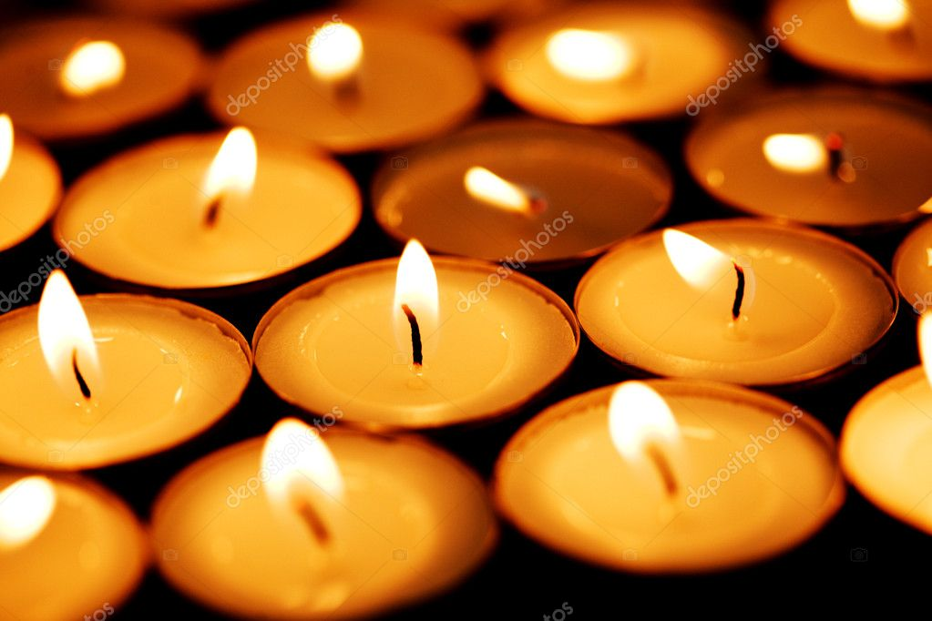 Tea light candles shining through darkness. — Stock Photo #9548804