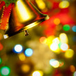 Christmas Gold bells with ribbon with colorful lights close up — Stock Photo