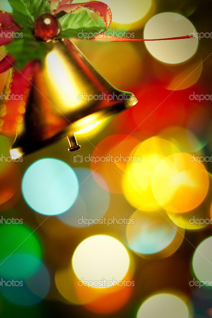 Christmas Gold bells with ribbon with colorful lights and decorations.  Stock Photo #9604416