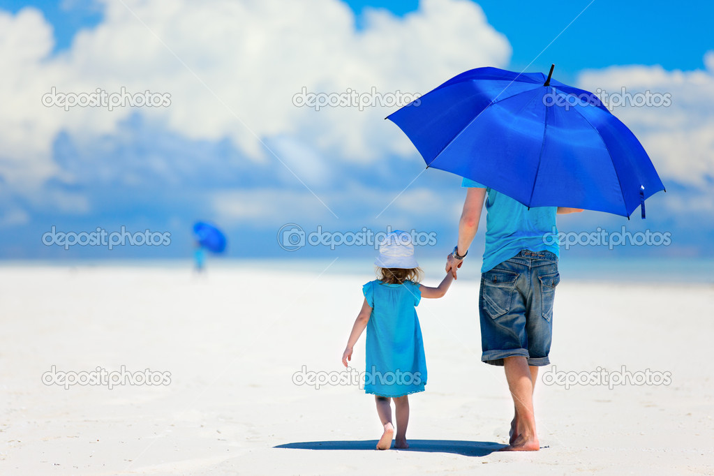 Father and daughter at beach with umbrella to hide from sun — Stock Photo #10146485