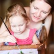 Mother and daughter painting a batik - Stock Photo