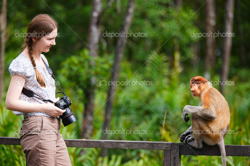 Female photographer and proboscis monkey on Borneo island in Malaysia — Stock Photo #9649451