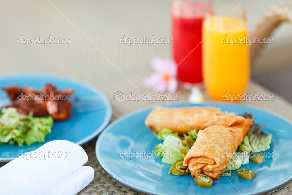 Two plates of delicious asian food and two glasses of fresh juices — Stock Photo #9694160