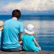 Father and kids sitting on wooden dock — Stock Photo #9785584