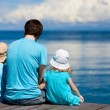 Father and kids sitting on wooden dock - Stock Photo