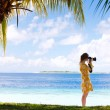 Young woman taking photos at beach — Stock Photo #9921181