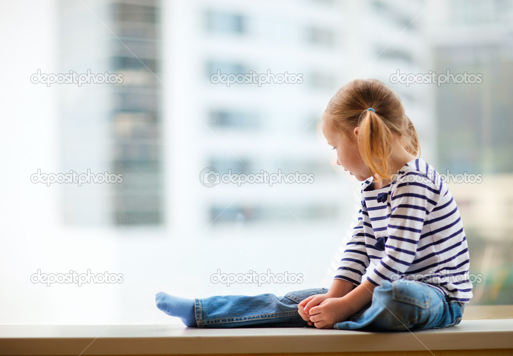 Adorable little girl sitting by the window — Stock Photo #9991069