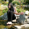 The girl sitting on a stone — Stock Photo