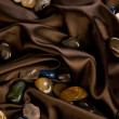 Color precious stone on brown silk - Stock Photo