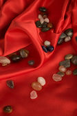 Color precious stone on red silk — Stock Photo