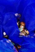 Color precious stone on blue fiber — Stock Photo