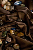 Color precious stone on brown silk — Stock Photo