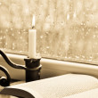 Royalty-Free Stock Photo: A book and a candle on a rainy day - sepia