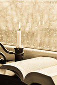 A book and a candle on a rainy day - sepia — Stock Photo