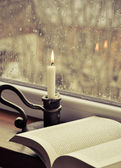 A book and a candle on a rainy day — Stock Photo