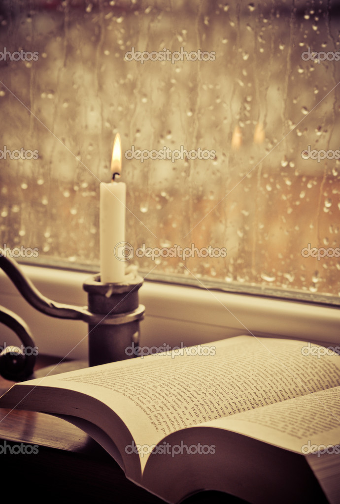 A book and a candle on a rainy day  Stock Photo #10106580