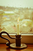 A stylized picture of a lit candle on a rainy day — Stock Photo