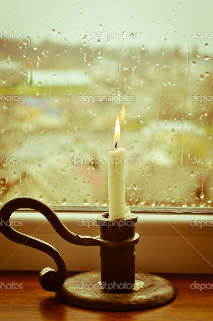 A stylized picture of a lit candle on a rainy day — Stockfoto #10157537