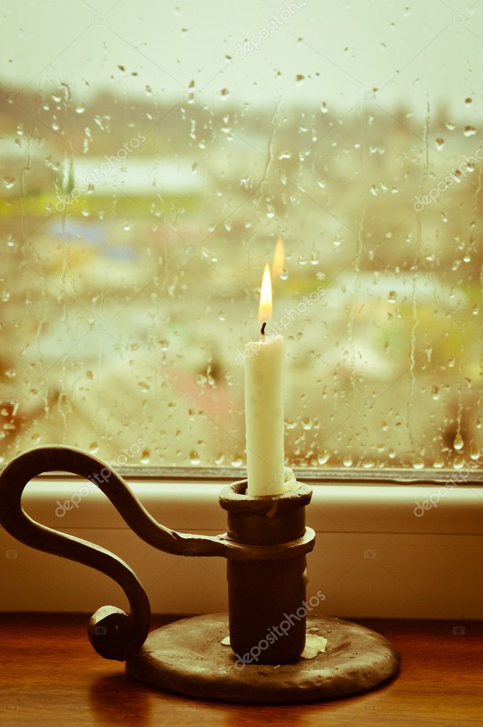 A stylized picture of a lit candle on a rainy day   #10157537