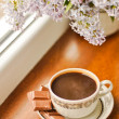 Ceramic cup with coffeeб chocolate and bouquet of lilac — Stock Photo #10501364
