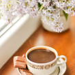 Ceramic cup with coffeeб chocolate and bouquet of lilac - Stock Photo