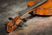 Close-up picture of the old violin on a silver fabric — Stock Photo