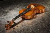 Old violin on a silver fabric — Stock Photo