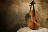 Old italian violin on a wall backround — Stock Photo